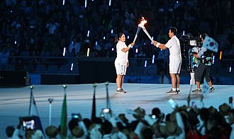 2014 Asian Games - The torch relay during opening ceremony. South Korean athletes Inbee Park move fire to Lee Seung-yeop
