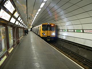 A Merseyrail train painted with a yellow front and grey sides. It is underground at Liverpool Central station.