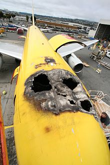 The top of a fire damaged airplane with several holes burnt through the top.