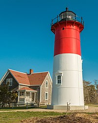 Red and white lighthouse next to a house