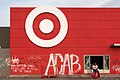 A man sits on a Target ball in front of the store on Thursday morning. The store was looted and graffitied after a night of protests in Minneapolis, Minnesota (49945856206).jpg