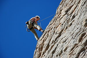 A person abseils down the crag.