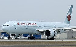 "Twin-engine passenger jet on the ground. It is white with ""AIR CANADA"" in red on its side."
