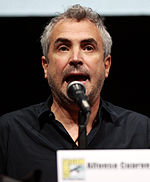 A Mexican male wearing a black unbuttoned shirt is seen speaking into a microphone.
