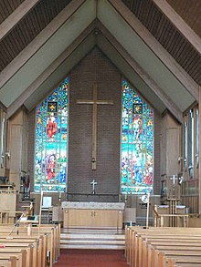 The interior of a building, with a vaulted ceiling supported by wood beams. The far end shows the back wall, which has a large wooden cross hung on a wall between two stained glass windows. An altar is visible before the wall, with a central path leading from it to the foreground, adjacent ot which are rows of pews.