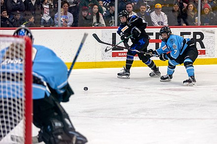 Members of the Buffalo Beauts and the Minnesota Whitecaps during the 2019 Isobel Cup championship game for the NWHL Amy Menke takes a shot at the goal with Emily Pfalzer.jpg