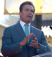Arnold Schwarzenegger wearing a blue suit and standing at a podium. He is facing away from the camera, smiling, and is clapping.