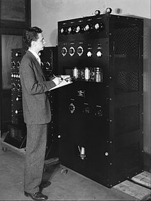 Aurthur A Collins standing next to a transmitter.