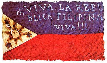 "Early flag of the Filipino revolutionaries (""Long live the Philippine Republic!""). The first two constitutions were written in Spanish. Bandera 03.jpg"
