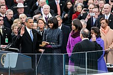 Barack Obama holds his right hand in the air as Michelle Obama looks at him and Malia and Sasha Obama watch as a man whose back is to the camera looks down.