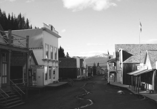 Barkerville's main street, taken in June 2004, showing the historic buildings and a small stream of water flowing down its sloped, unpaved, roads