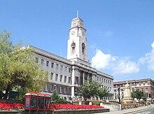 Barnsley Town Hall em um belo dia.  A própria Câmara Municipal é visível por trás de alguns jardins;  o edifício é feito de pedra branca e tem uma torre do relógio impressionante