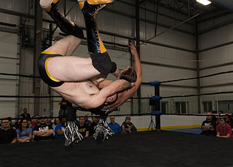 Oney Lorcan - Busick executing a running somersault neckbreaker against Nick Jackson