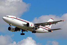 A white plane with red and green cheat lines across its fuselage with landing gears down shown against a blue sky with some clouds