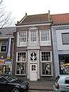 foto van Pand met verdieping en dwars zadeldak. De lijstgevel heeft een rijk gebeeldhouwde middenas in vroege Lodewijk XV-stijl