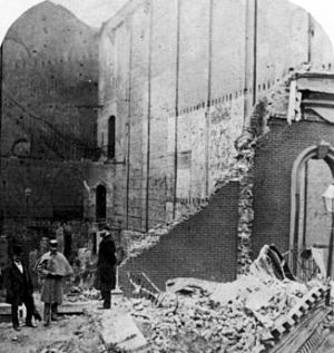 Brooklyn Theatre fire - Brooklyn Theatre from Johnson Street, looking south from the stage area toward the front of the house. On the south wall of the theatre ruins, above the man in the light grey cape, are diagonal markings. These trace the flight of stairs from the gallery down to the second floor corridor and which had once been attached to the south wall of the theatre. The stairs themselves collapsed in the fire. The uppermost opening into masonry on the extreme right, above the man with the top hat, marks where the gallery stairs continued down to street level. Between this opening and the south wall ran a short, north–south corridor.