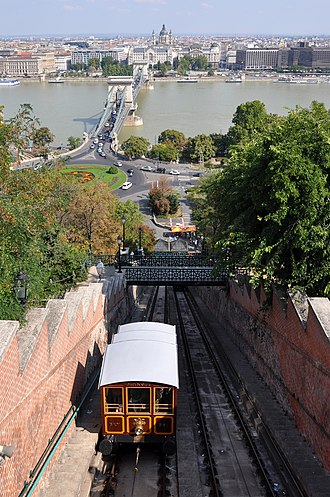 """Budapest Castle Hill Funicular - The Budapest funicular, with Car BS1 """"Margit"""" in the foreground and the Széchenyi Chain Bridge in the background"""