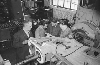 Scientific management - Photograph of East German machine tool builders in 1953, from the German Federal Archives. The workers are discussing standards specifying how each task should be done and how long it should take.