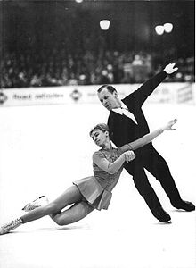 Two people are in a figure skating spin, the man is upright on the left, spinning the woman around himself.