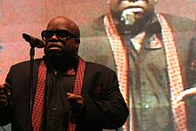 An African-American man wearing sunglasses sings into a microphone. In the background, the image of the same man is projected.