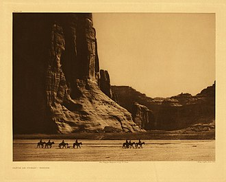Navajo Nation - Navajo. Seven riders on horseback and dog trek against background of canyon cliffs. Edward S. Curtis (1904)