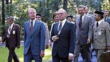 Carter, Begin, and Brzezinski walking together outside.