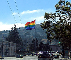 A color photograph of a large Gay Pride flag flying at the intersection of Market and Castro Streets and the hills of San Francisco in the distance