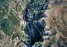 Jagged dark blue area of the gorge running form the bottom left to top right, surrounded by brown and green higher areas of land