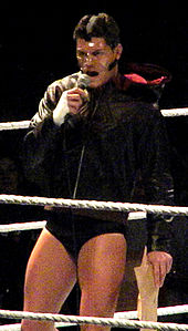 A dark-haired Caucasian male stands in a wrestling ring with grey ring ropes. He is wearing short black wrestling tights with a black, hooded jacket, and his face is covered with a clear plastic mask. He is holding a microphone to his mouth with his right hand, and in his left hand he is holding brown paper bags.