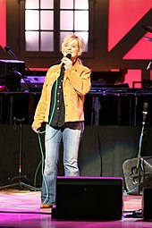 A blonde woman wearing a tan jacket, black shirt and blue pants, singing into a microphone