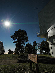 Laser being emitted from telescope observatory dome