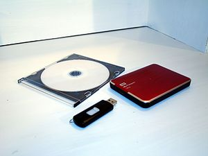 Backup - From left to right, a DVD disc in plastic cover, a USB flash drive and an external hard drive