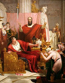 Damocles sits on a throne, looking apprehensively at a sword suspended above him. Dionysius is standing next to him and gestures at the sword. The two men are surrounded by servants, courtiers, and guards.