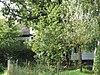 foto van Houten dwarshuis onder hoog pannen schilddak met dakkapel versierd met vleugelstukken en fronton