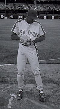"A man in a light baseball uniform with ""New York"" on the chest and a dark baseball cap."