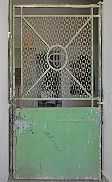 A jail door with a solid steel bottom and a grate on the top half