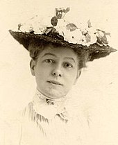 Black-and-white photograph of a woman in a high-necked white dress, wearing a flowered hat