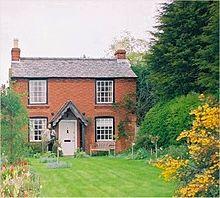 uma casa de campo de tijolos com um grande jardim frontal