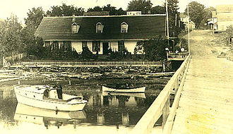 Comox, British Columbia - The Elk Hotel, built at the foot of the Comox wharf by Joseph Rodello in 1877. The photographer was standing on the pier facing the shore and Wharf Road.