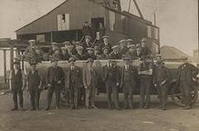 In a black and white photograph, group of 26 young to middle-aged men wearing suits and flat caps stand in two rows. Behind them is a large, industrial shed, and in the distance the roof of a house can be seen.