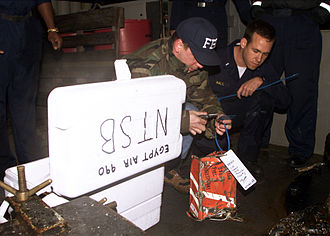 An FBI agent tags the cockpit voice recorder from EgyptAir Flight 990 on the deck of the USS Grapple (ARS 53) at the crash site on November 13, 1999. Fbi egypt air 990.jpg