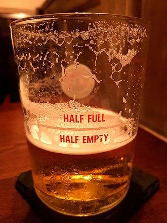 Theories of humor - A beer glass made by Camden Town Brewery (London). The physical presence of beer in the glass's lower part, exactly where the inscription is: 'HALF EMPTY', sets a collision between two frames of reference. This incongruity results in a humorous effect at the moment of its realization.