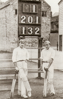A black and white picture of Lionel Palairet and Herbie Hewett stood in front of a scoreboard reading 1, 201, 132.