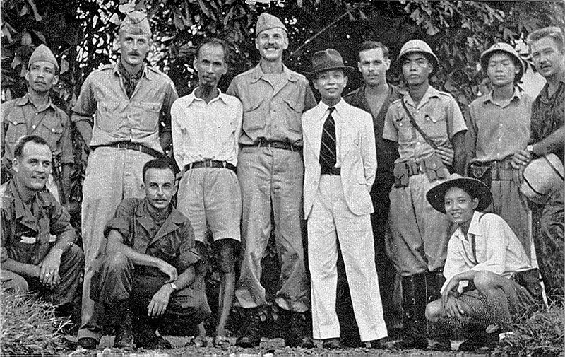 Accompanying two Việt Minh leaders, the OSS Deer Team in 1945. From l. to r.: René Defourneaux, Ho Chi Minh, Allison Thomas, Võ Nguyên Giáp, Henry Prunier and Paul Hoagland, far right. Kneeling, left, are Lawrence Vogt and Aaron Squires