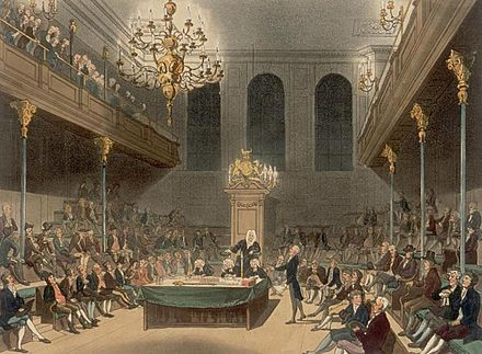 "The House of Commons early 19th century. The Loyal Opposition occupy the benches to the Speaker's left. Seated in the front, the leaders of the opposition form a ""Shadow Government"", complete with a salaried ""Shadow Prime Minister"" ready to assume office if the government falls or loses the next election. House of Commons Microcosm.jpg"
