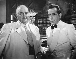 Black-and-white film screenshot of two men, both wearing suits. The man on the left is older and is nearly bald; the man on the right has black hair. In the background several bottles of alcohol can be seen.