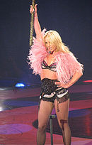 A female blond performer. She wears a black lingerie ensemble underneath a pink fur vest. Her left hand is on her left hip while her right hand is holding a big mallet.