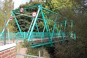 A photograph of a triangle-truss vehicular bridge spanning a river