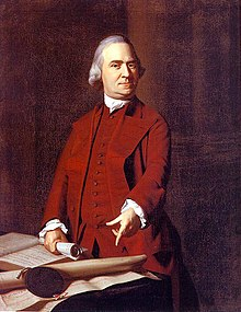 A stern middle-aged man with gray hair and wearing a dark red suit. He is standing behind a table, holding a rolled up document in one hand, and pointing with the other hand to a large document on the table.