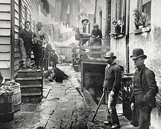Slum - One of the many New York City slum photographs of Jacob Riis (ca 1890). Squalor can be seen in the streets, wash clothes hanging between buildings.